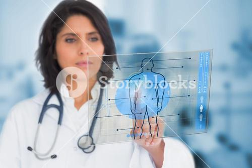 Serious female doctor touching a touchscreen