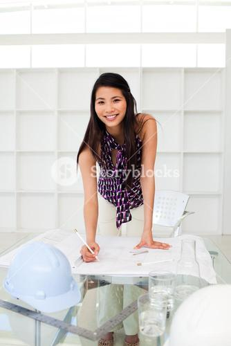 Attractive female architect studying blueprints