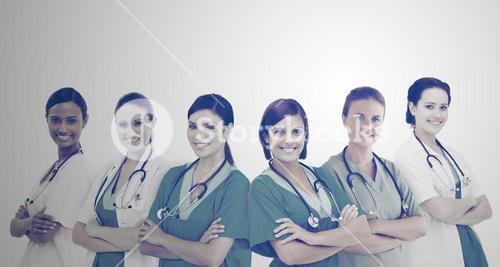 Female hospital workers standing arms folded in line