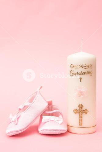 Christening candle with pink baby booties