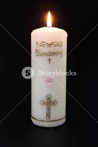 Lit white christening candle with pink detail