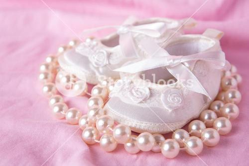 White baby booties with string of pearls