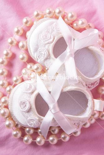 Overhead of white baby booties with string of pearls