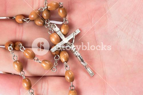 Rosary beads in someones hand