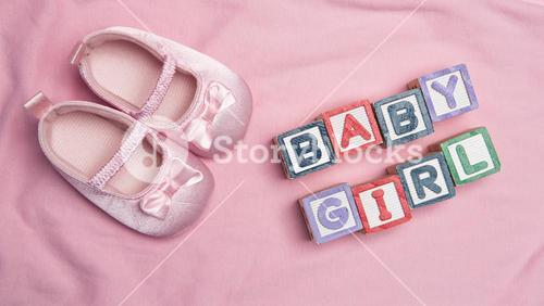 Baby girl spelled out in blocks with pink booties