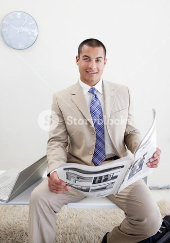 Charming manager reading a newspaper
