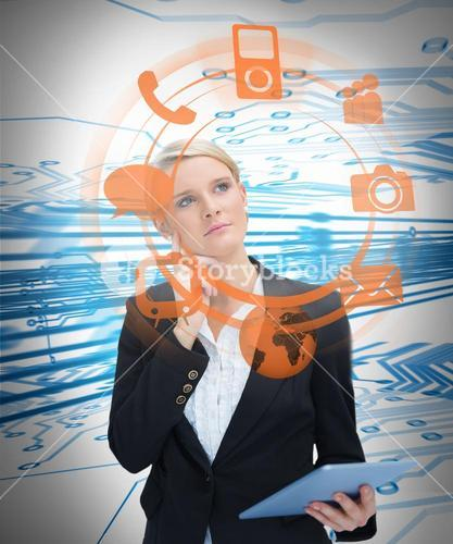 Businesswoman considering various applications and holding tablet