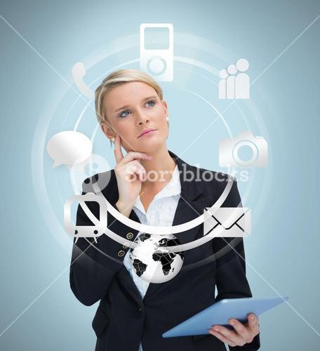 Thoughtful businesswoman with tablet pc considering applications