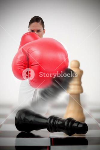 Woman in boxing gloves knocking over chess pieces