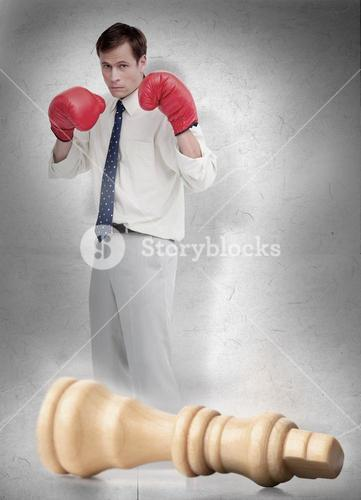 Businessman in boxing gloves with knocked over chess piece