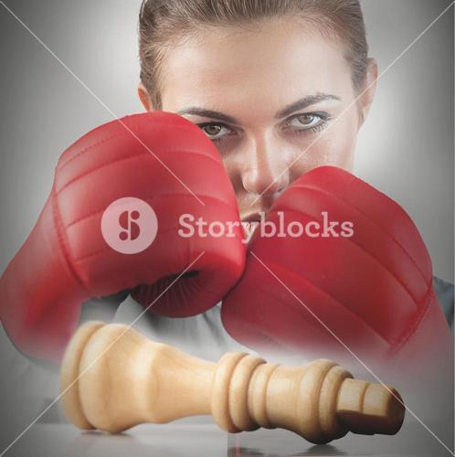 Powerful female boxer with knocked chess piece