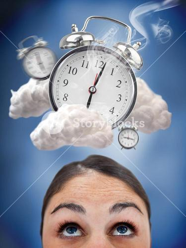 Woman looking up at ringing alarm clocks in clouds