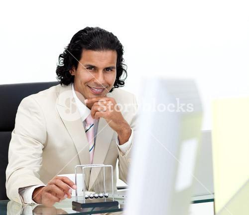 Portrait of an businessman having fun with kinetic balls