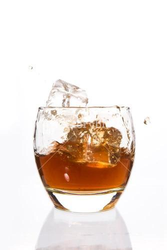 Ice cubes falling in a tumbler of whiskey