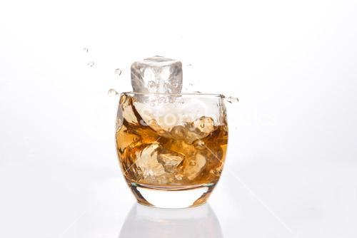 Ice cube falling in a tumbler of whiskey