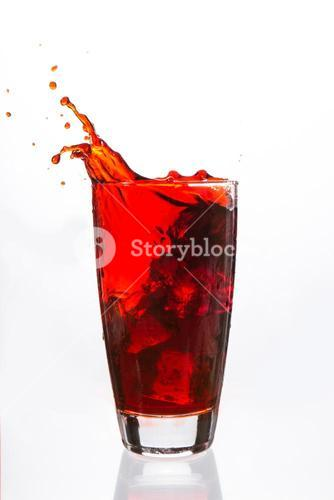 Ices cubes falling in a glass filled with red liquid