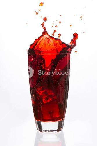Ices cubes falling in a glass of red liquid