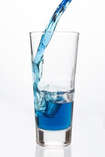 Glass being filled with blue liquid