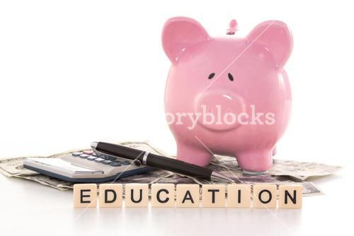 Piggy bank beside calculator and education spelled out in plastic letter pieces
