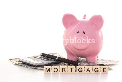 Piggy bank beside calculator and mortgage spelled out in plastic letter pieces