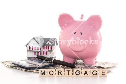 Piggy bank beside calculator miniature house and mortgage spelled out in plastic letter pieces