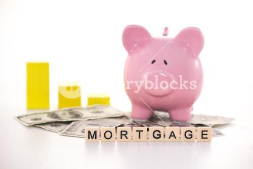 Piggy bank beside graph and mortgage spelled out in plastic letter pieces