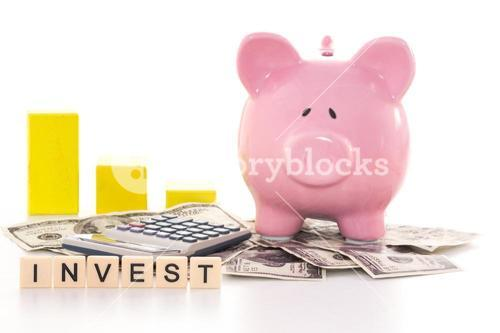 Piggy bank beside graph calculator and invest spelled out in plastic letter pieces