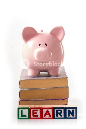 Piggy bank standing on stack of books with learn spelled out in blocks