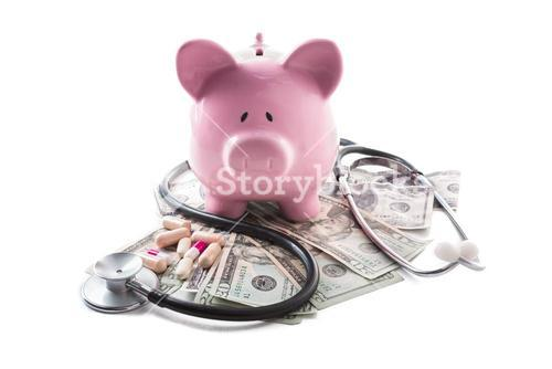 Piggy bank tablets stethoscope resting on pile of dollars