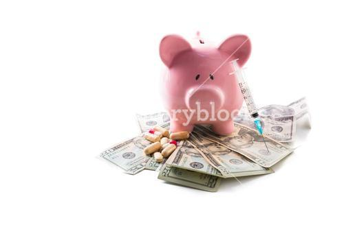 Piggy bank tablets and syringe resting on pile of dollars