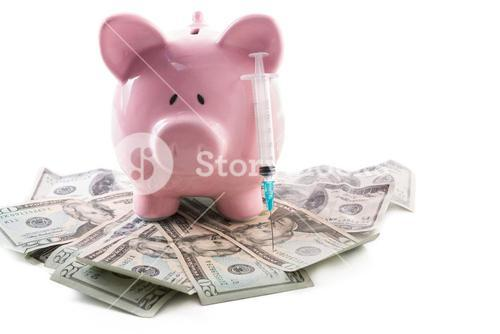 Piggy bank and syringe sitting on a pile of dollars