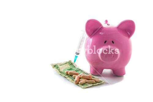 Syringe leaning against piggy bank with dollars and pills