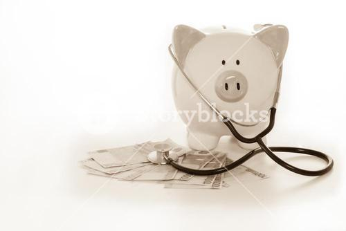 Piggy bank sitting on pile of dollars with stethoscope