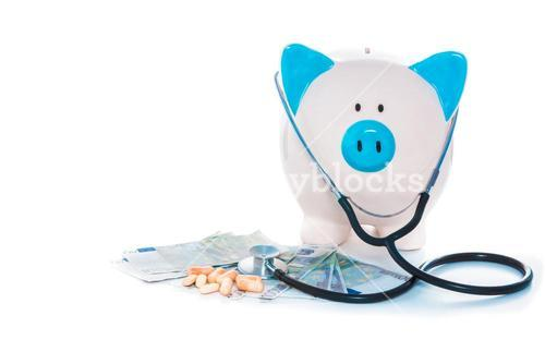 Piggy bank sitting on pile of dollars with stethoscope and pills