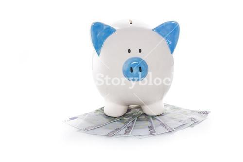 Hand painted blue and white piggy bank on pile of euros