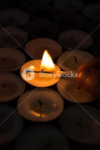 Hand lighting candle with match