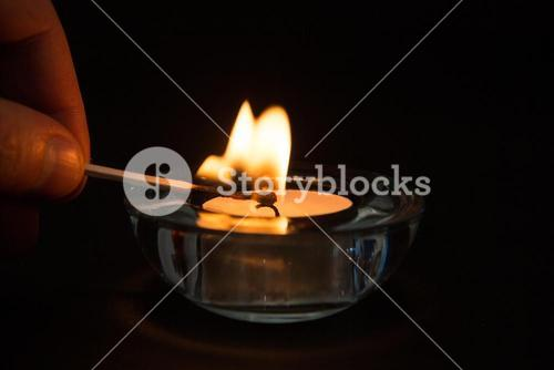 Hand lighting tea light candle in the dark