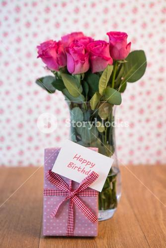 Bunch of pink roses in vase with pink gift leaning against it and happy birthday card