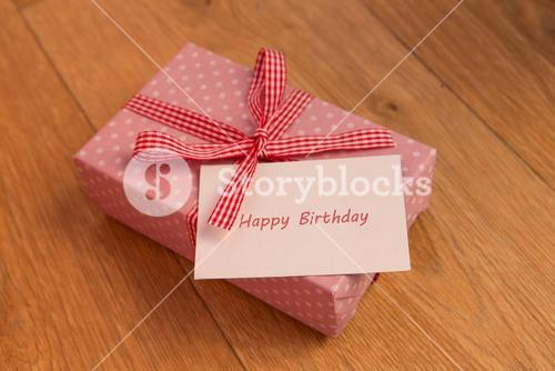 Pink wrapped present with birthday card greeting