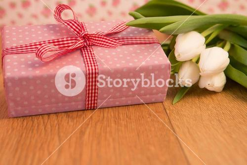 Pink wrapped present with bunch of white tulips