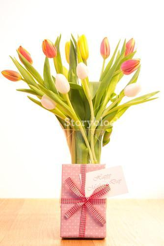Vase of tulips on wooden table with mothers day gift