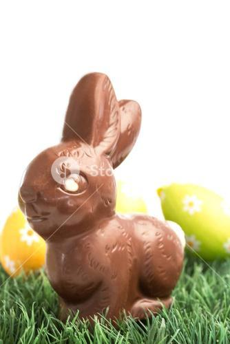 Chocolate bunny rabbit sitting on grass with easter eggs behind