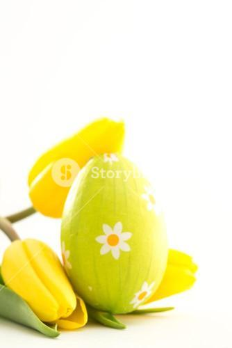 Green easter egg with yellow tulips