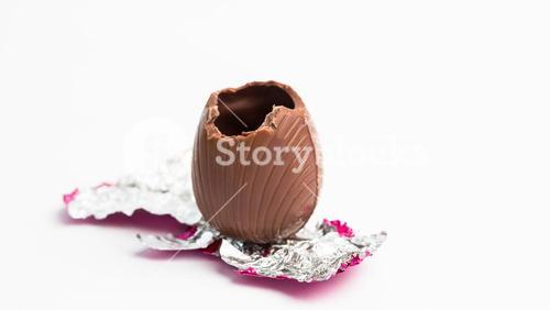 Easter egg unwrapped in pink foil with bite taken out