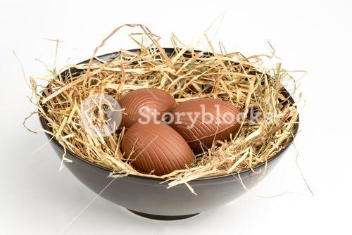 Chocolate easter eggs in straw in bowl