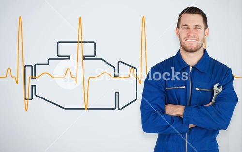 Portrait of a young mechanic next to background with car engine and heart line
