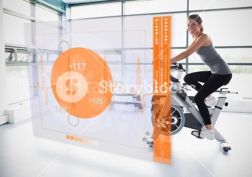 Young girl doing exercise bike with futuristic interface showing calories