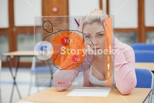 Blonde woman thinking hard while studying on interface with brain