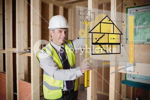 Architect using spirit level and looking at hologram interface