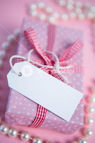 Pink gift wrapped box with blank tag and pearls